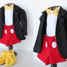 yellow slippers, white shirt, yellow bow tie, red shorts with white polka dots, and a black jacket
