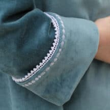 close up of cuffed coat sleeve in teal velveteen with white pom pom trim