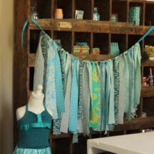 strips of various blue fabrics tied on ribbon hanging across cubby furniture