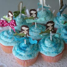 cupcakes on white cake platter with blue frosting and paper mermaid cutouts on top