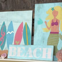 "multiple beach themed signs stacked against one another - surfboards, ""BEACH"", mermaid, and seashells"