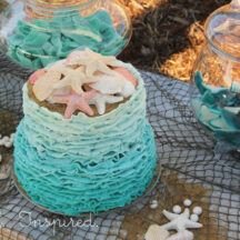 blue wavy ocean themed cake with candy seashells on top, sitting on fish net with jars with shark candy in background