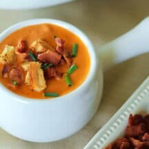 tomato soup with croutons, chives, and bacon bits in white handled crock