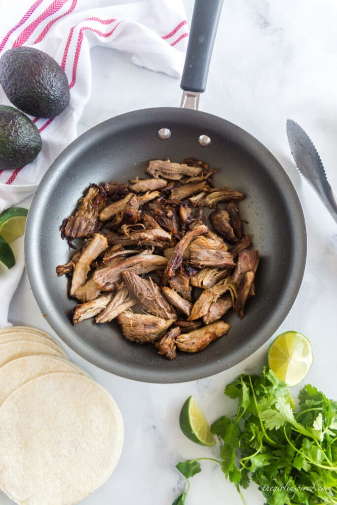 browned carnitas in frying pan, avocados, tortillas, cilantro, and lime