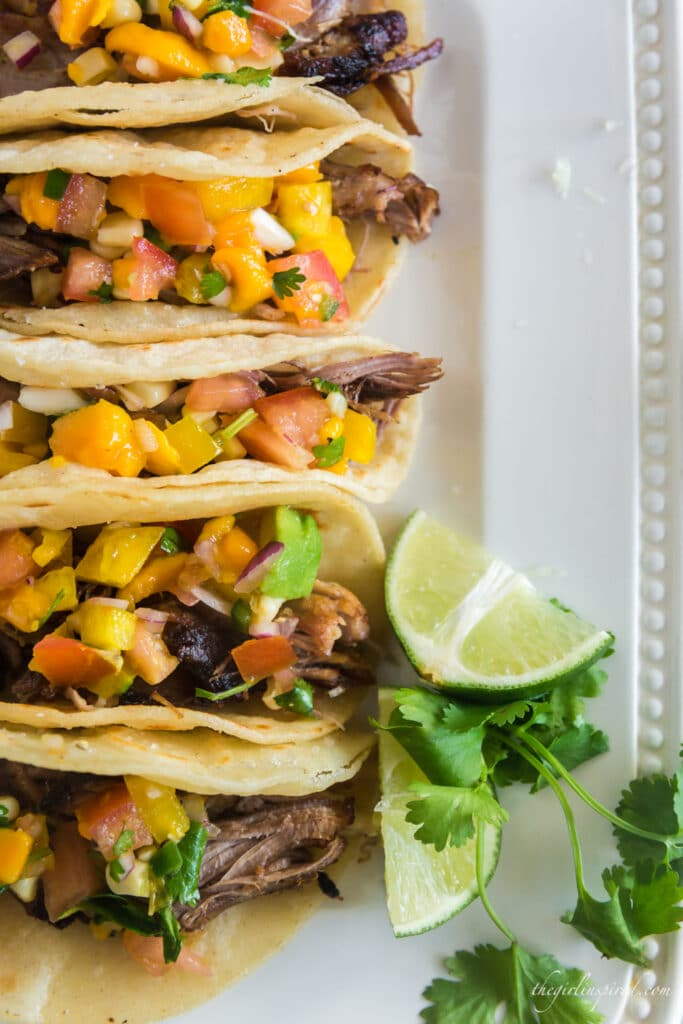 line of carnitas tacos on white plate with mango salsa, lime wedge, and cilantro