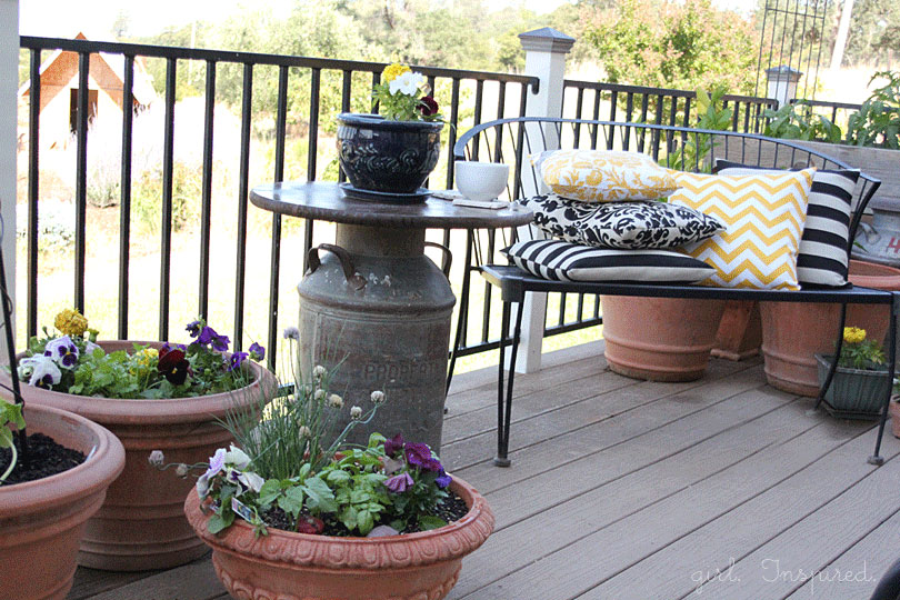 Wooden top outdoor side table with antique milk can base, blue pot of flowers and white mug on table, black bench with yellow and black throw pillows, potted flowers on deck