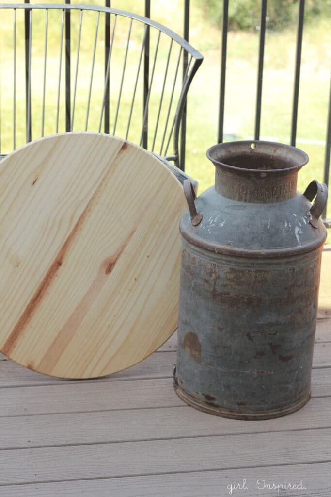 wooden round and antique milk can sitting on outdoor deck