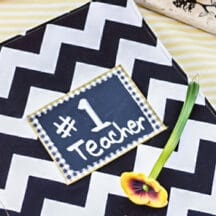black and white zig zag notebook cover with #1 Teacher chalkboard label, flower pen, on white and yellow tablecloth
