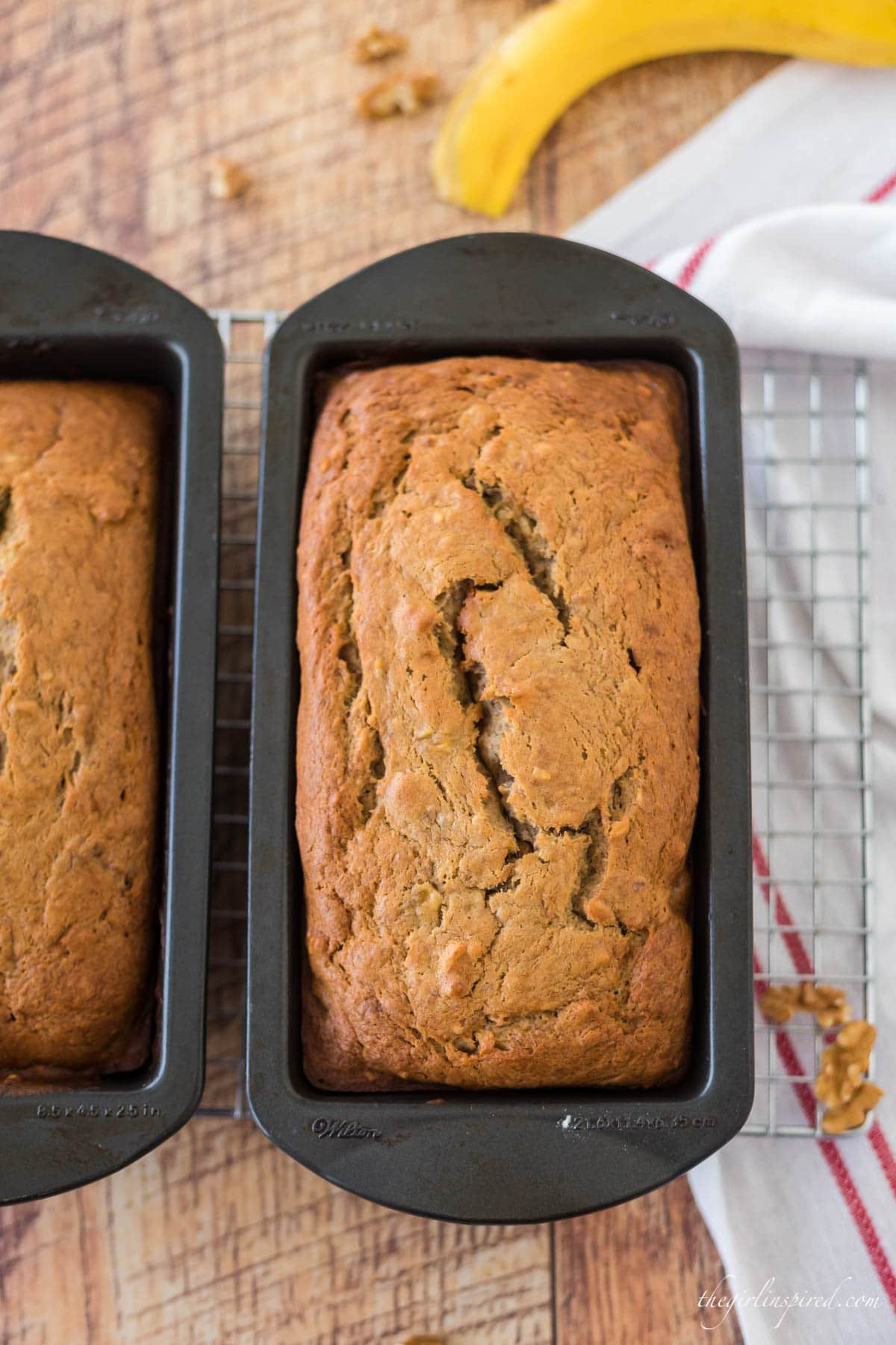 banana nut bread loaves in pan on cooling rack, with banana peel and tea towel