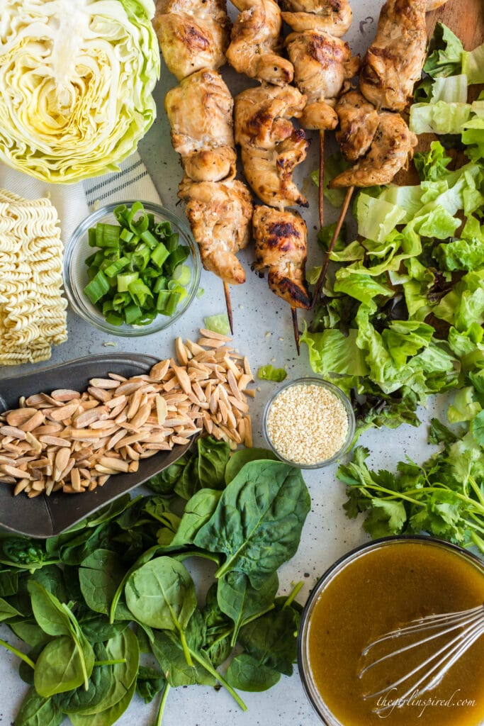 overhead view of chinese chicken salad ingredients: spinach, lettuce, green onions, almond slivers, top ramen noodles, cabbage, sesame seeds, cilantro, and bowl of dressing with whisk
