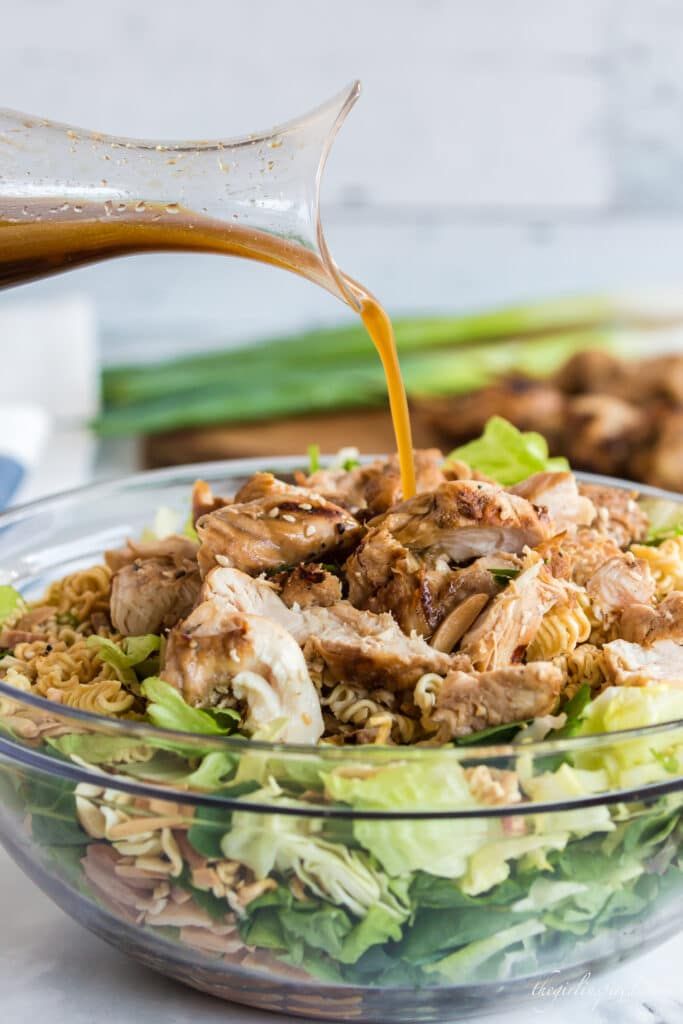 dressing pouring onto chicken piled on salad in glass bowl