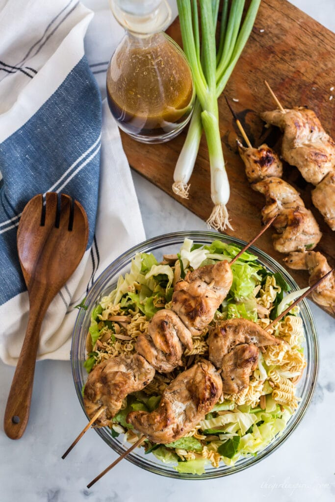 overhead view of skewered chicken on top of salad in glass bowl, cutting board with green onions and chicken skewers, wooden serving spoon, blue and white towel, and cruet of dressing
