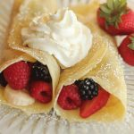 Breakfast Crepes with berries and whipped cream on glass plate