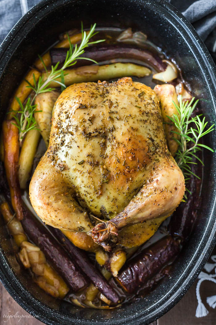 whole roasted chicken in black roasting pan with rainbow carrots and fresh herbs