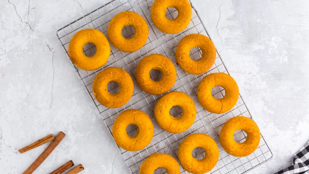 overhead of two ingredient pumpkin donuts on cookie sheet with cinnamon sticks