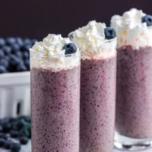 three tall glasses filled with blueberry kale smoothie and blueberries in white basket and bananas in the background
