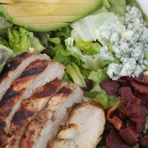 sliced, grilled chicken, crumbled bacon, blue cheese, and avocado slices on a bed of lettuce