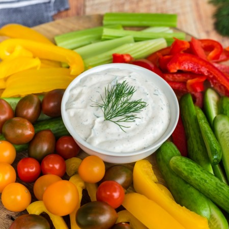white bowl of dill dip with tomatoes, colored bell peppers, and celery on wooden cutting board