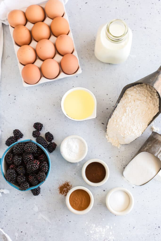 Ingredients for Blackberry Muffins: fresh blackberries in blue cup, crate of brown eggs, metal scoops with flour and sugar, white dishes holding oil, cinnamon, cloves, salt, and baking powder