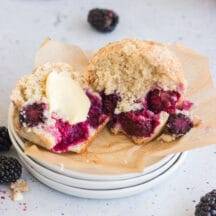 blackberry muffin on stack of white plates split open with butter in the middle and blackberries around