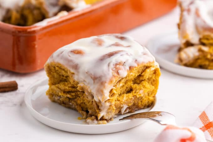 cinnamon roll on white plate in front of baking dish