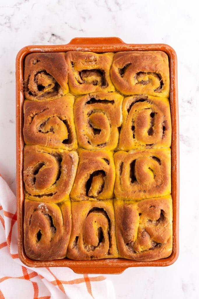 overhead photo of cooked pumpkin cinnamon rolls in orange baking dish with orange and white linen