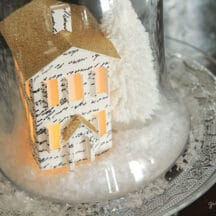 miniature paper house with gold roof, snow and white tree on glass plate with glass cloche over the top