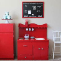 red kids play kitchen, red framed chalkboard, and white baby high chair