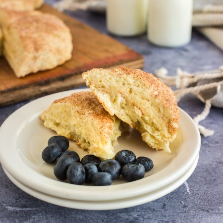 two buttermilk scones stacked on white plates with blueberries, milk and wooden board with scones in background