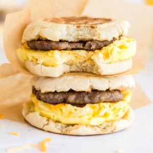 two stacked breakfast sandwiches with parchment wrappers and bite taken from one