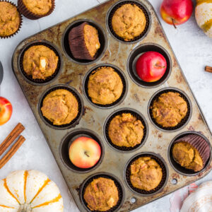 overhead of pumpkin apple muffins in muffin tin with red apples, pumpkins, and cinnamon sticks around