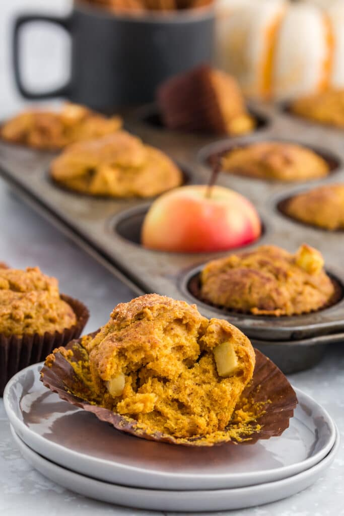 pumpkin apple muffin split open on plate in front of muffin tin with red apples, pumpkins, and cinnamon sticks