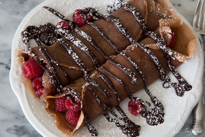 Chocolate crepes with raspberries inside, drizzled with chocolate sauce, sprinkled with powdered sugar, served on a white plate.