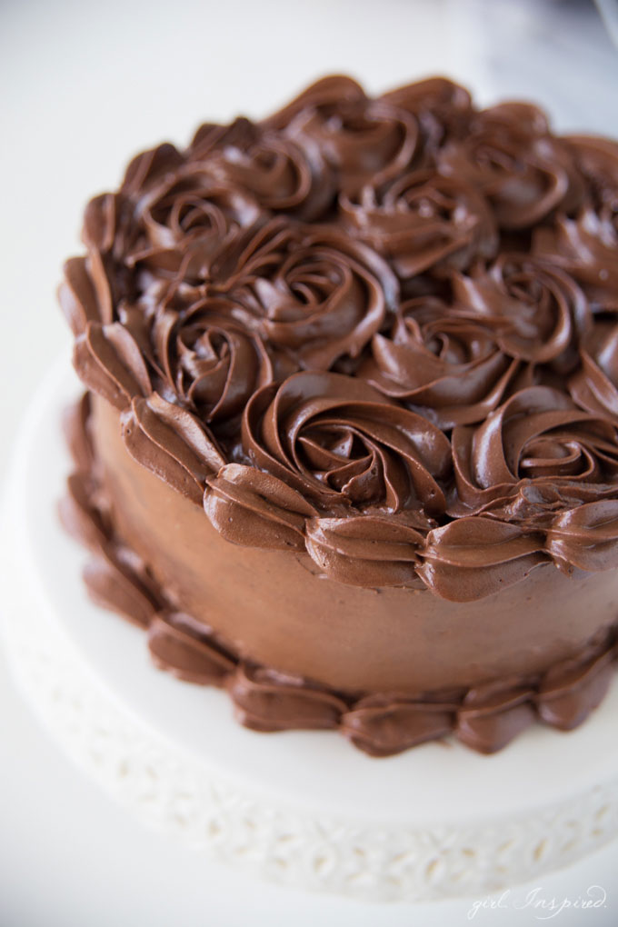 dark chocolate frosting piped in swirls on cake on white platter