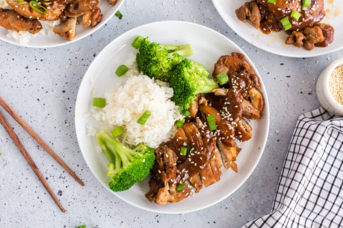 overhead view of teriyaki chicken on white plate with broccoli and rice, sesame seeds and green onion garnish