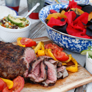 grilled and sliced tri-tip on wooden cutting board with veggies, paper plates and utensils, bowl of red and blue tortilla chips
