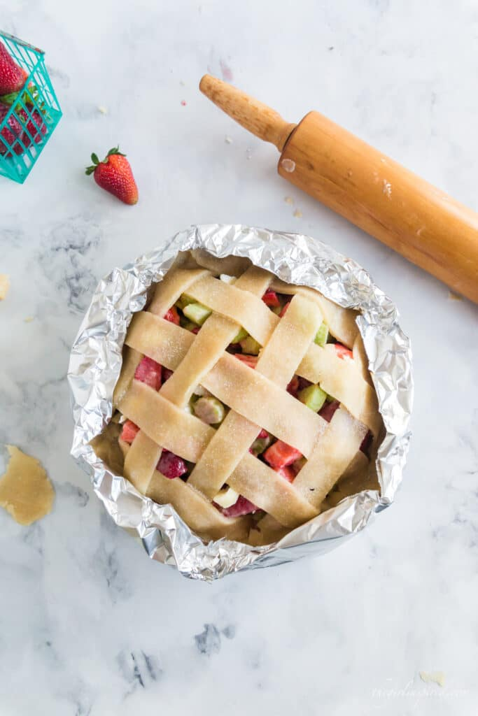 overhead photo of pie prepared to bake with aluminum foil wrapped around the crust, wooden rolling pin and strawberries in background