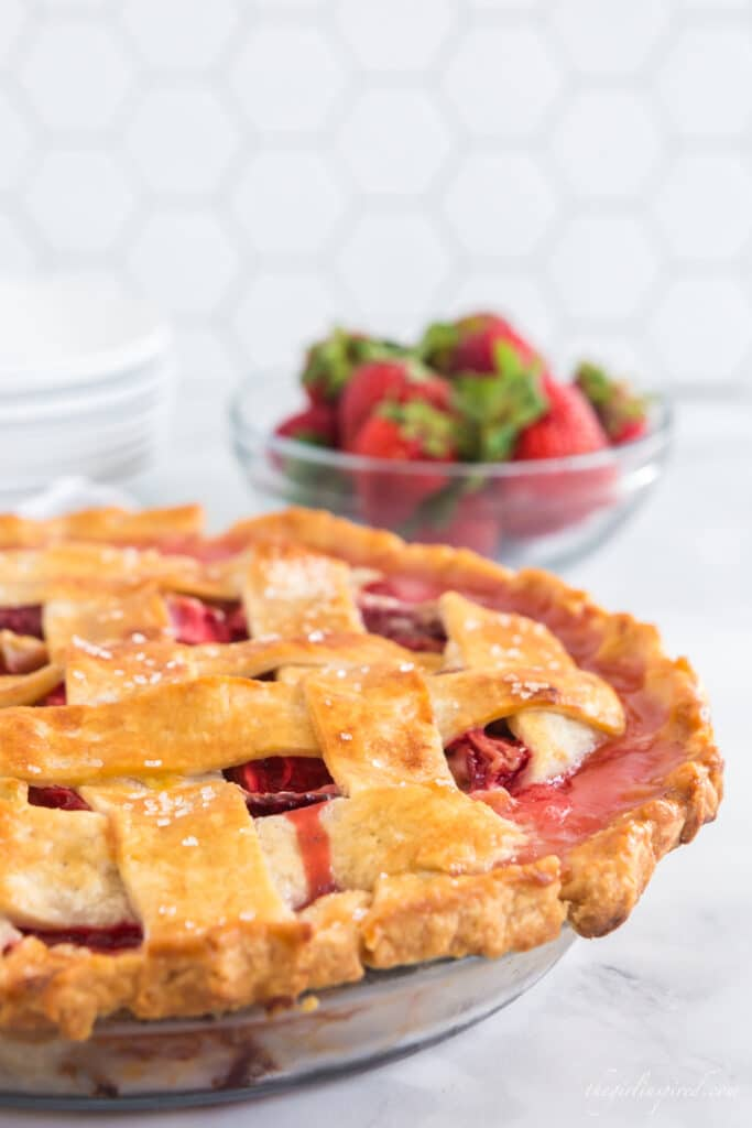 baked strawberry rhubarb pie, a glass bowl of strawberries, a stack of white plates