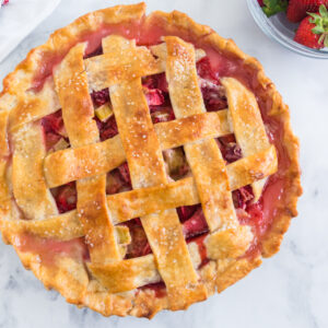 overhead photo of baked strawberry rhubarb pie, a glass bowl of strawberries, a stack of white plates and a red and white linen