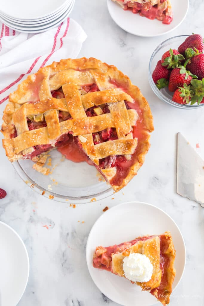 photo of baked strawberry rhubarb pie, a plated slice of pie with vanilla ice cream on top, a glass bowl of strawberries, a stack of white plates and a red and white linen