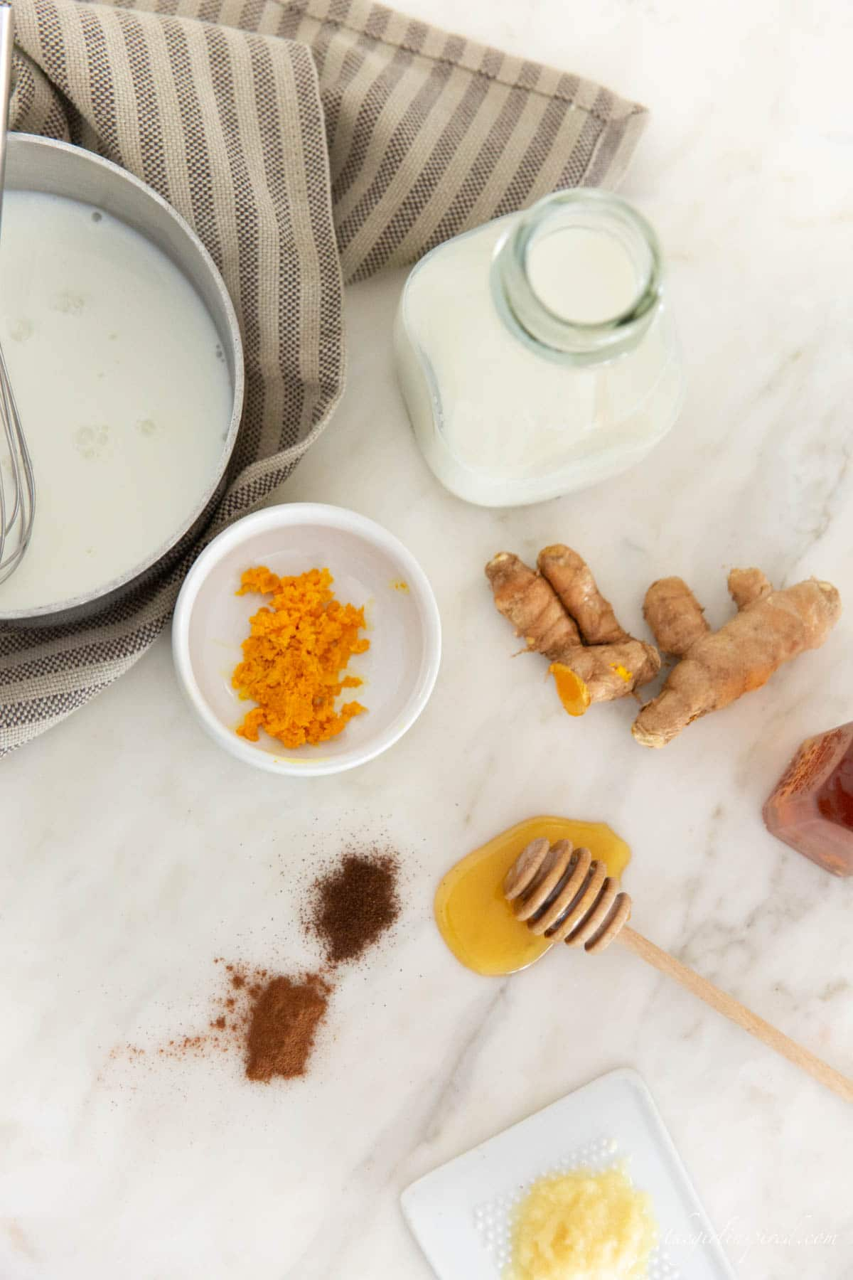 ingredients including grated and whole turmeric, honey, cinnamon and clove spices, a glass jar of milk, dish towel and saucepan with milk and a whisk