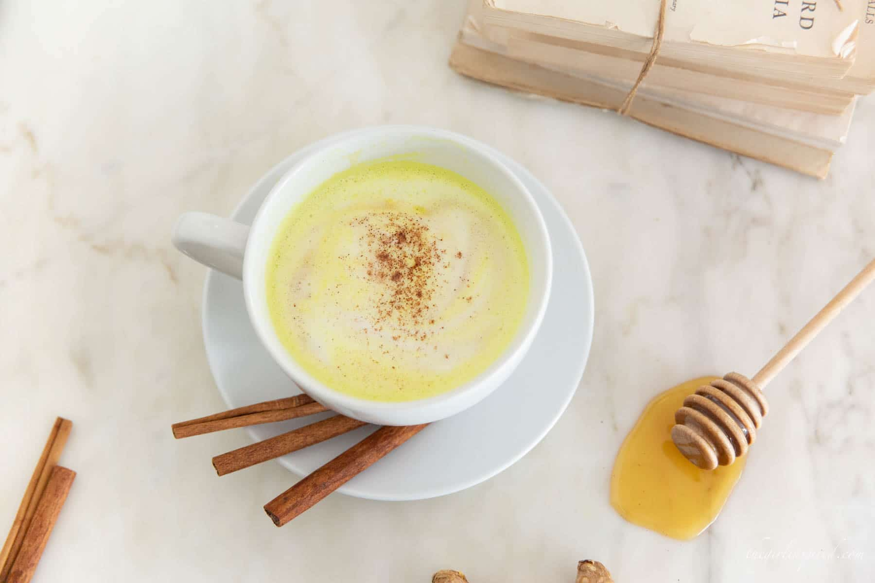 frothy yellow milk in white mug with cinnamon sticks, whole turmeric root, cinnamon sticks, and honey