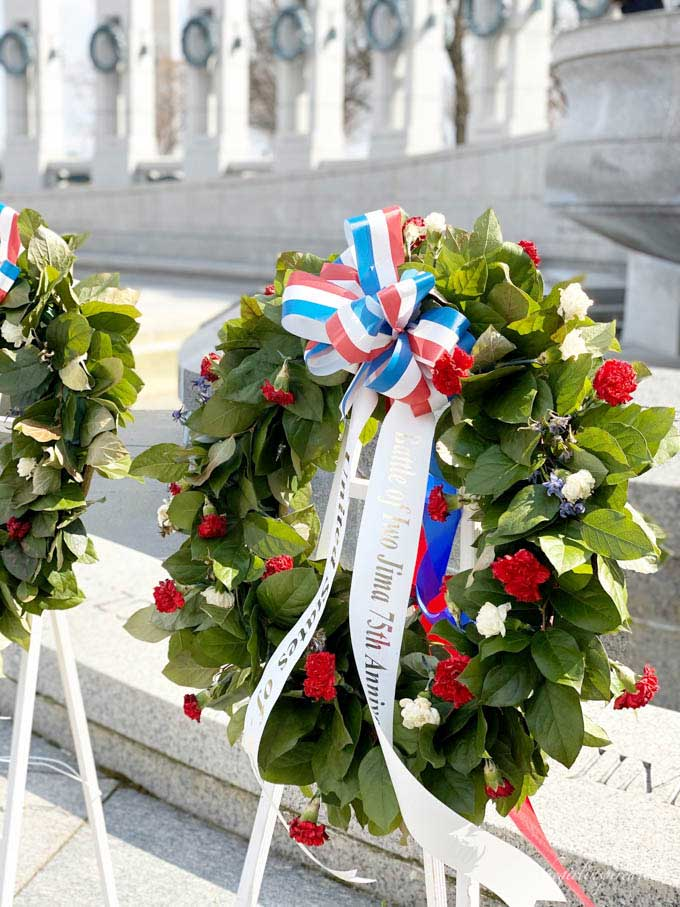 floral wreath with red and white flowers and red, white, and blue ribbon in front of World War II memorial in Washington DC