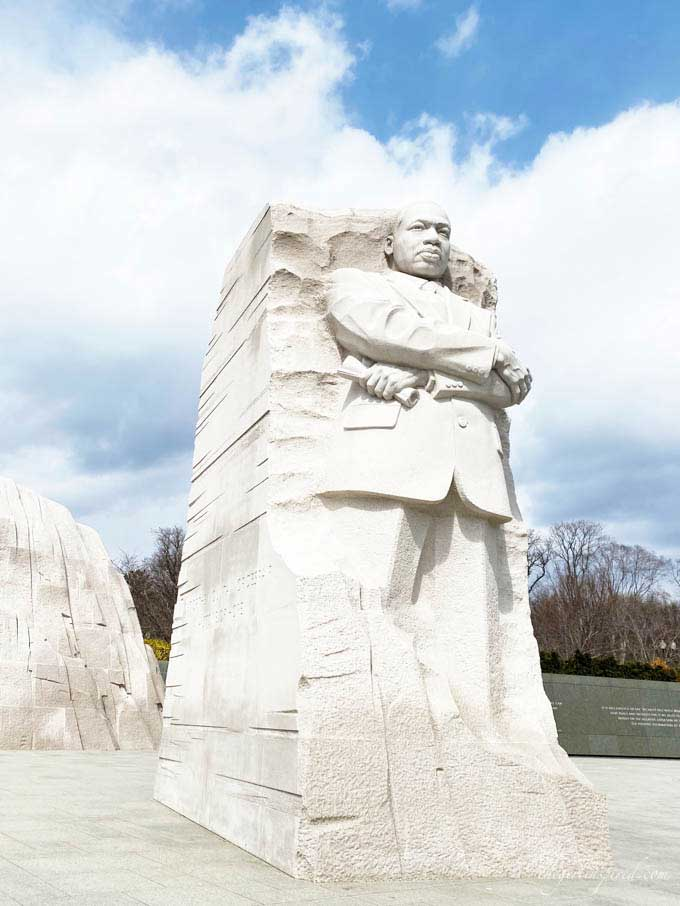 white stone carving of MLK with cloudy blue sky background in DC