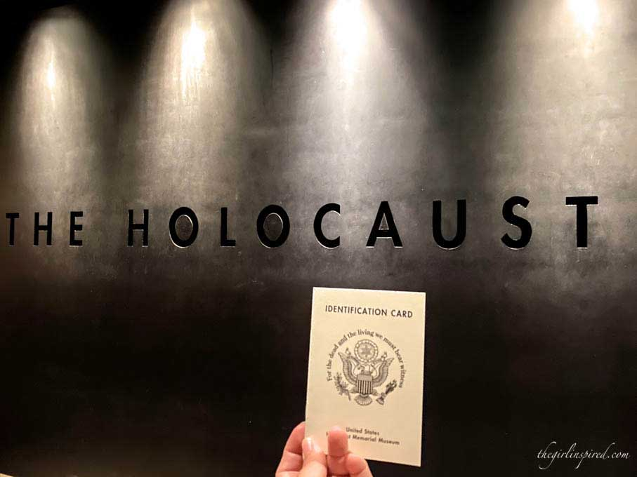 "Small white booklet held in front of wall engraved ""Holocaust"""