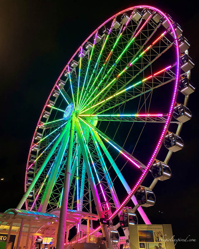 pink, green, and blue illuminated Ferris wheel against black sky