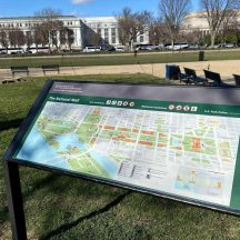 close up of park map with grass and museum buildings in the background