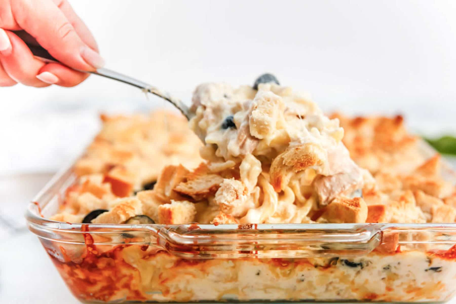 spoonful of baked tuna casserole in glass baking dish