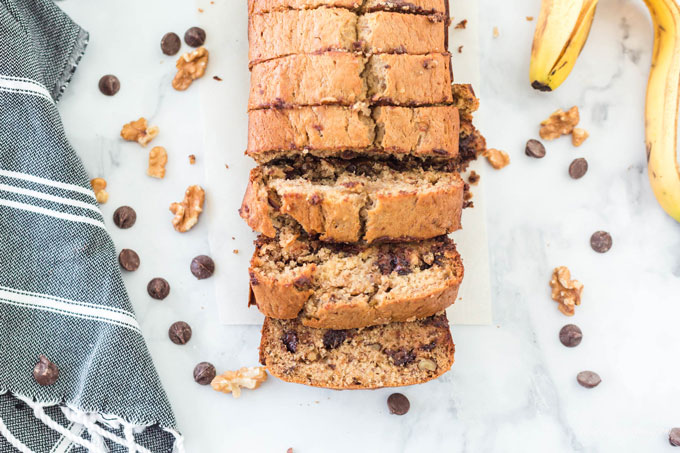 sliced chocolate chip banana bread on marble counter with walnuts, chocolate chips, banana peel, and grey dish towel
