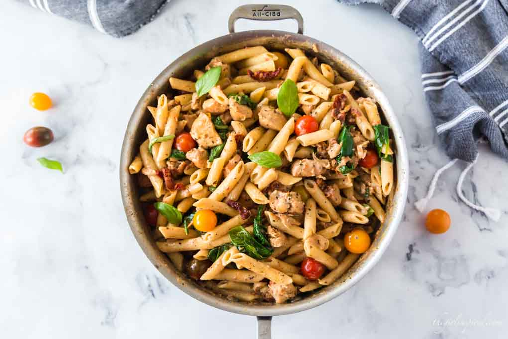 creamy chicken pasta in saucepan with grey dishtowel